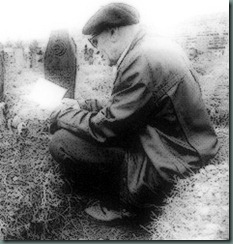 Man reading by grave in cemetery